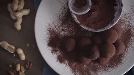 pinda s : Craft chocolate truffles on plate with cocoa powder and peanuts.