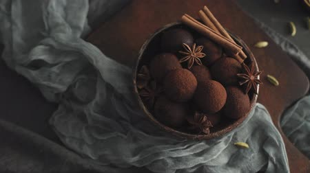 yermantarı : Craft chocolate truffles on plate with cocoa powder and peanuts.
