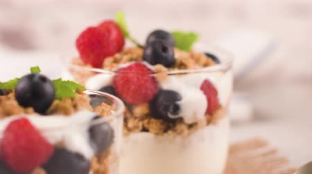 borůvka : Granola blackberries and raspberries homemade yogurt in glass on light white wooden background. Healthy food concept.