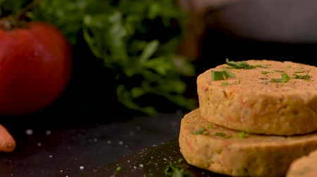 строгий вегетарианец : Raw veggie burger with chickpeas and vegetables with parsley leaves on kitchen countertop. Стоковые видеозаписи