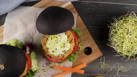 countertop : Tasty grilled veggie burgers with chickpeas and vegetables on black bread on dark wooden countertop. Stock Footage