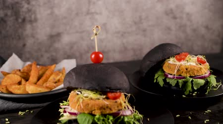 cuisine dark : Tasty grilled veggie burgers with chickpeas and vegetables on black bread on dark wooden countertop. Stock Footage