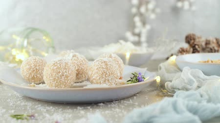 프랄린 : Homemade candies with coconut roasted almonds on a Christmas season table decorated with lights and stars.
