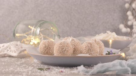 yermantarı : Homemade candies with coconut roasted almonds on a Christmas season table decorated with lights and stars.