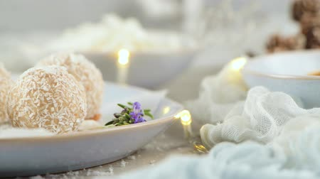 yermantarı : Homemade candies with coconut roasted almonds on a Christmas season table decorated with lights. Stok Video