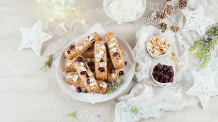 corn flakes : Cereal bars with almonds, coconut and cranberries on a Christmas season table decorated with lights. Stock Footage