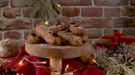 arandanos rojos : Cereal bars with almonds, coconut and cranberries on a Christmas season table decorated with lights. Archivo de Video