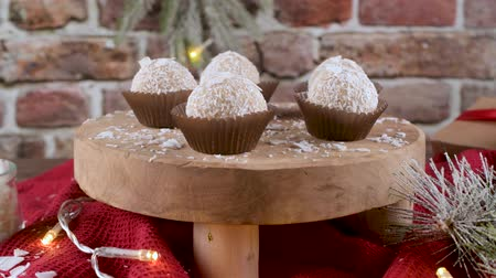 pralina : Homemade candies with coconut roasted almonds on a Christmas season table decorated with lights. Vídeos