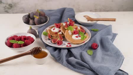 american cuisine : Healthy summer breakfast, homemade classic american pancakes with fresh berry, yogurt and honey, morning light stone background.