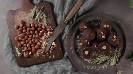 pralina : Dark chocolate truffles with hazelnuts and chopped hazelnuts over wooden cutting board. Vídeos