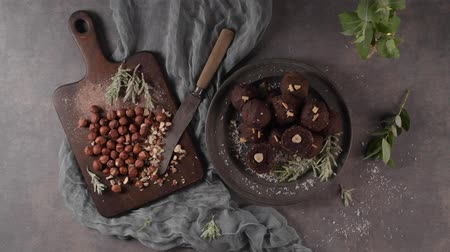 trufa : Dark chocolate truffles with hazelnuts and chopped hazelnuts over wooden cutting board. Vídeos