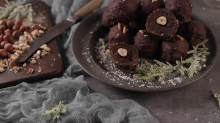 tartufo : Dark chocolate truffles with hazelnuts and chopped hazelnuts over wooden cutting board. Filmati Stock