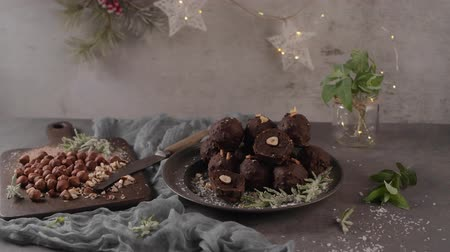 tekercselt : Dark chocolate truffles with hazelnuts and chopped hazelnuts over wooden cutting board. Stock mozgókép