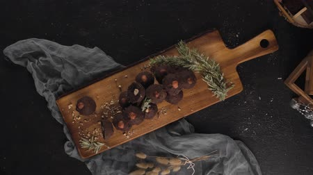 프랄린 : Dark chocolate truffles with hazelnuts over wooden cutting board.