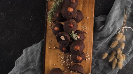 trufa : Dark chocolate truffles with hazelnuts over wooden cutting board.