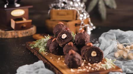 tekercselt : Dark chocolate truffles with hazelnuts over wooden cutting board.
