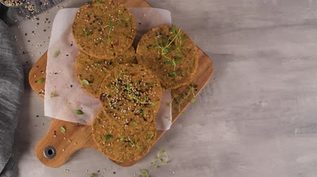 Raw veggie burger with lentils, dry tomato and thyme on wood cutting board. Stok Video