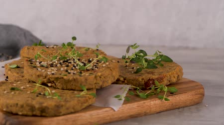 Raw veggie burger with lentils, dry tomato and thyme on wood cutting board. Dostupné videozáznamy