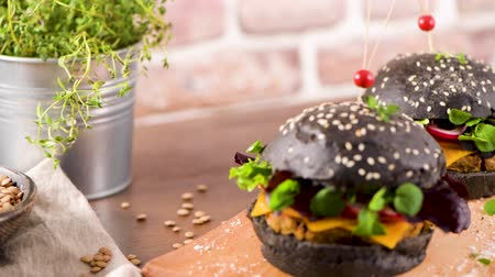 tomilho : Tasty grilled veggie burger with lentils, dry tomato and thyme with black bread on wooden countertop.