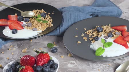 crocante : Ripe blueberries and strawberries with yogurt and granola in plate on a light grey background. Healthy Eating.