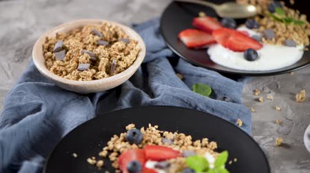 Ripe blueberries and strawberries with yogurt and granola in plate on a light grey background. Healthy Eating.
