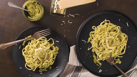 spinaci : Fresh spaghetti with basil pesto and cheese on dark kitchen countertop background.