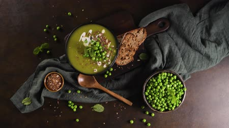 Green pea soup with linseed and pumpkin and sunflower seeds on a rustic kitchen countertop. Stock Footage