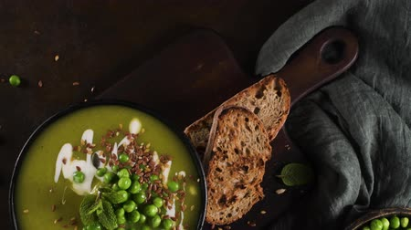 Green pea soup with linseed and pumpkin and sunflower seeds on a rustic kitchen countertop. Stok Video