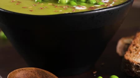 Green pea soup with linseed and pumpkin and sunflower seeds on a rustic kitchen countertop. Dostupné videozáznamy