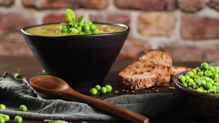 peas : Green pea soup with linseed and pumpkin and sunflower seeds on a rustic kitchen countertop. Stock Footage