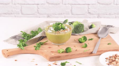 peas : Broccoli soup in a glass bowl on a kitchen countertop with slices of the stems.