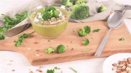 zupa groszek : Broccoli soup in a glass bowl on a kitchen countertop with slices of the stems.