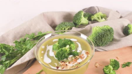 Broccoli soup in a glass bowl on a kitchen countertop with slices of the stems.