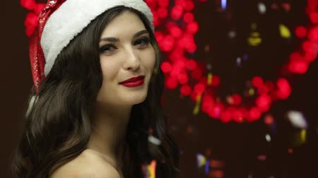 gorgeous : Santa girl smiling to camera and watching how confetti falling