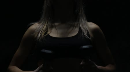 темно : Woman with dumbbells in dark background Стоковые видеозаписи