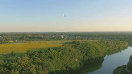landing field : Aerial Paraplane hang glider in the air above river city canyon