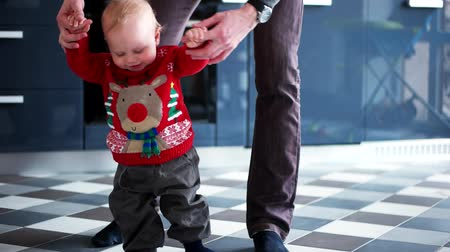 ilk : Baby girl  1 year old  walking his first step with his fathers help Stok Video