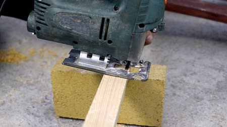 Worker sawing a wooden block jigsaw Wideo