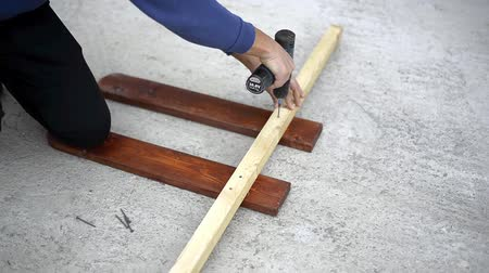 csavarhúzó : Worker drill twists the screwdriver screws in a wooden block