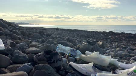 Polluted shore, garbage on the beach, empty plastic bottles, rubber shoes