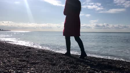 A woman walks along the beach in Sunny weather