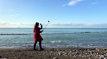 A woman with a selfie stick walks by the sea, records a video for the blog Dostupné videozáznamy