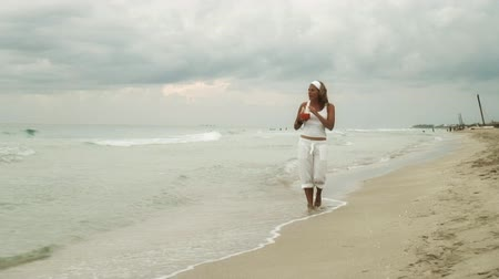 приморский : video of a woman dressed in white, enjoying a walk on the beach while having a cocktail at dusk