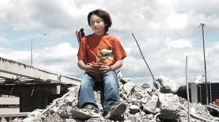 architecture and urbanism : HD video of a young boy holding a plant surrounded by the urban jungle and destruction