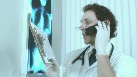 sebész : Video of a doctor studying a patient X Ray and exam result while speaking in a cellular phone with an other doctor in an hospital room Stock mozgókép