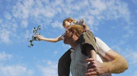 ailelerin : A father holding his son on his shoulder in front of an animated sky background