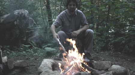 şenlik ateşi : Man seated in front of a campfire Stok Video