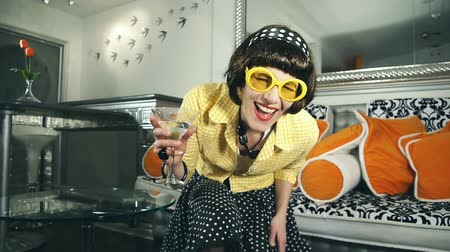 pijany : Eccentric fashionable woman laughing while having a cocktail in a retro futuristic interior
