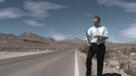 perdido : One single man on a desert empty road holding a carboard sign with GOING NOWHERE written  on it Vídeos