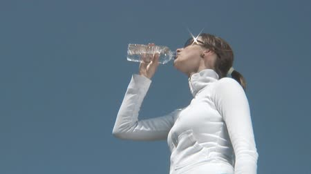 umysł : healthy woman drinking water out of a plastic bottle in front of a sky background with wind playing in her hair.